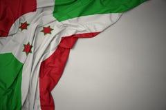 Vinkande nationsflagga av Burundi på en grå bakgrund arkivbild
