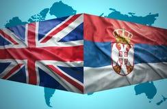 Vinkande serb- och brittflaggor royaltyfri fotografi
