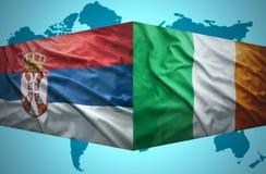 Vinkande serb- och irländareflaggor royaltyfri fotografi