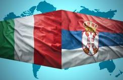 Vinkande serb- och italienareflaggor royaltyfria foton