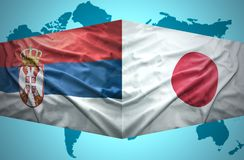 Vinkande serb- och japanflaggor arkivbild