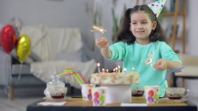 Vinkande tomtebloss för liten flicka i bakgrunden av kakan arkivfilmer