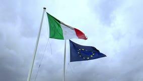 Vinkande tygtextur av flaggan av Italien och fackliga Europa på blå himmel med moln,