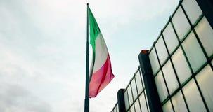 Vinkande tygtextur av flaggan av Italien på blå himmel med moln,