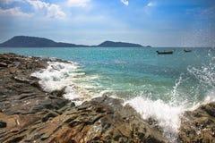 Vinkar avbrott på en stenig strand som bildar en sprej royaltyfria bilder