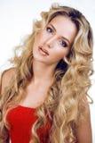 Vinkar den blonda kvinnan för skönhet med långt slut för lockigt hår som upp isoleras, frisyr hollywood som ler lyckligt livsstil Royaltyfria Bilder