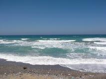 Vinkar det blåa havet för havet på stranden Sandig strand havsvatten det fästande ihop isolerade banahavet shells white Blåtthav, Royaltyfria Bilder