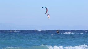 Vinkar på stranden Blått hav, blå himmel Kitesurfing Kiteboarding, surfare på stranden stock video