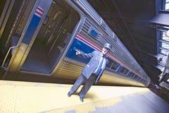Vinkelsikten av ledaren på den Amtrak drevplattformen meddelar alla ombord på ostkustdrevstationen på vägen till New York City, N Royaltyfri Bild