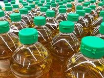 Vinkelsikten av matlagning gömma i handflatan olja i plast- flaskor med det gröna locket arkivfoton