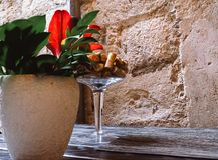 Vinkopp med korkar och vas med blommor i en tabell i en restaurang Original- garnering i en svart tabell royaltyfria bilder