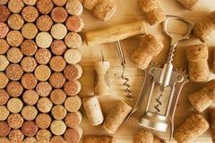 Vinkorkar och två korkskruv på träbakgrunden royaltyfri foto