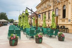 Vinkovci town in Croatia. VINKOVCI, CROATIA - MAY 14, 2018 : Empty coffee bar terrace in the King Zvonimir street in city center of Vinkovci, Croatia royalty free stock photo