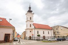Vinkovci town in Croatia. VINKOVCI, CROATIA - MAY 14, 2018 : People passing by the Catholic church in city center of Vinkovci, Croatia stock images