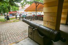 Vinkovci town in Croatia. VINKOVCI, CROATIA - MAY 14, 2018 : People passing by an old metal cannon which is set outside of the city museum building in Vinkovci royalty free stock image