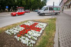 Vinkovci town in Croatia. VINKOVCI, CROATIA - MAY 14, 2018 : A red cross sign made from flowers set up in front of the red cross building in Vinkovci, Croatia royalty free stock image