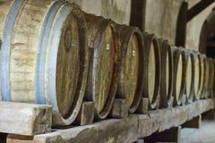 Vinlagring i gamla wood trummor i källare Arkivbild