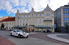 Vinlius downtown. VILNIUS, LITHUANIA - AUGUST 11: Retro limousine crosses the main square of old town on August 11, 2012. Vilnius is the capital of Lithuania Stock Photo
