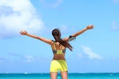 Vinnande bekymmerslös konditionkvinna som uttrycker lycka på strandsommarsemester Arkivfoto