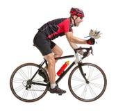 Vinnande cyklist som rider en cykel med blomman Arkivfoton