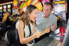 Vinnande kasinoenarmad bandit för man och för kvinna royaltyfri fotografi