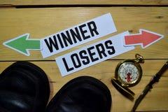 Vinnare eller förlorare mitt emot riktningstecken med kängor, glasögon och kompasset på trä fotografering för bildbyråer