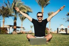 Vinnare Stiligt mansammanträde på gräset och bruksbärbara datorn med seger lyftte händer på palmträdbakgrund Sommarkall royaltyfri fotografi
