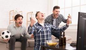 vinnarear Upphetsade vänner som hemma håller ögonen på fotboll royaltyfri bild