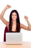 Vinnarebrunettflicka med en bärbar dator Arkivfoto