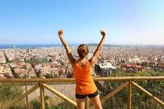 Vinnarekonditionkvinnan kommer till överkanten av Barcelona och tycka omcityscape från belvedere Upphetsad attraktiv ung kvinna i Arkivbild