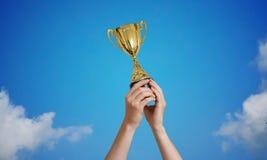 Vinnaren rymmer en trofé i händer mot blå himmel royaltyfri bild