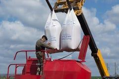 Vinnitsa/Украина - 04/19/2018: человек раскрывает сумки семян приостанавливанных над бурильщиком против неба Стоковые Изображения