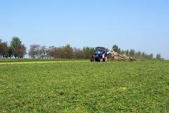 Vinnitsa/de Oekraïne - 05/04/2018: De tractor met de eenheidsritten rond het gebied en verzamelt het felling van groen veevoeder royalty-vrije stock fotografie