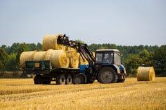 Vinnitsa, Ucraina - luglio 26,2016 Trattore enorme che raccoglie mucchio di fieno Immagini Stock Libere da Diritti