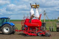 Vinnitsa/Ukraina - 04/19/2018: Gaffeltrucken lyftte stora påsar av frö ovanför drillborren till traktoren, och mannen hällde jämn Royaltyfri Foto