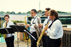 Vinnitsa,Ukraine - 23 August,2016.Gold saxophone with specks on. It in male hands.The musical collective plays a concert,jazz music concept Royalty Free Stock Photos