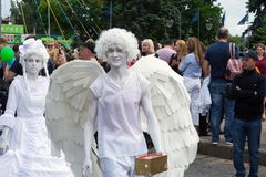 A living statue of an angel walks down the street amid people, at the celebration of Europe Day stock photography