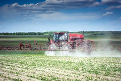 Self-propelled sprayer makes herbicide on the field of young corn. Vinnitsa/Ukraine - 05/22/2018: self-propelled sprayer makes herbicide on the field of young royalty free stock photography