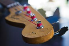 Vinnytsia, Ukraine - 09.20.2015: headstock and pegheads with strings of legendary Squier Fender bass guitar royalty free stock photos