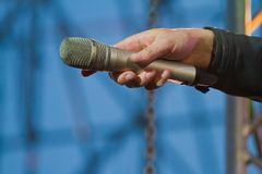 Vinnytsia, Ukraine - 04.25.2014: Sennheiser E965 microphone in a hand of singer turned to the audience royalty free stock photos