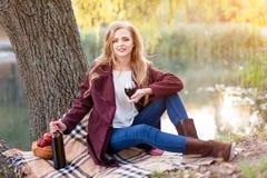 Vino bevente della bella donna all'aperto che ha picnic nel parco Ritratto di giovane bellezza bionda che gode di un vetro di Immagini Stock