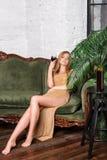 Vino bevente della donna Bella giovane donna bionda in vestito da sera dorato lungo con vetro di vino rosso in sottotetto di luss Fotografie Stock Libere da Diritti