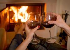 Vino bevente delle coppie davanti ad un fuoco Fotografia Stock