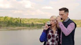 Vino bevente delle coppie vicino al grande lago Data romantica stock footage