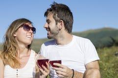Vino bevente delle giovani coppie felici sopra alla montagna Immagine Stock Libera da Diritti