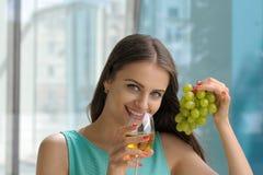 Vino bianco bevente e sorridere della ragazza Immagini Stock Libere da Diritti