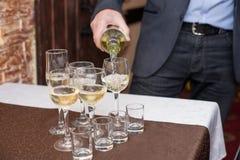 Vino bianco di versamento del sommelier maschio nei bicchieri di vino dal gambo lungo fotografie stock