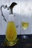 Vino bianco in lanciatore del vino dell'oggetto d'antiquariato e di vetro Immagine Stock