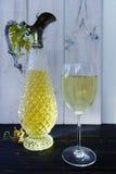 Vino bianco in lanciatore del vino dell'oggetto d'antiquariato e di vetro Immagini Stock