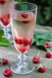Vino blanco con las frambuesas frescas Foto de archivo libre de regalías
